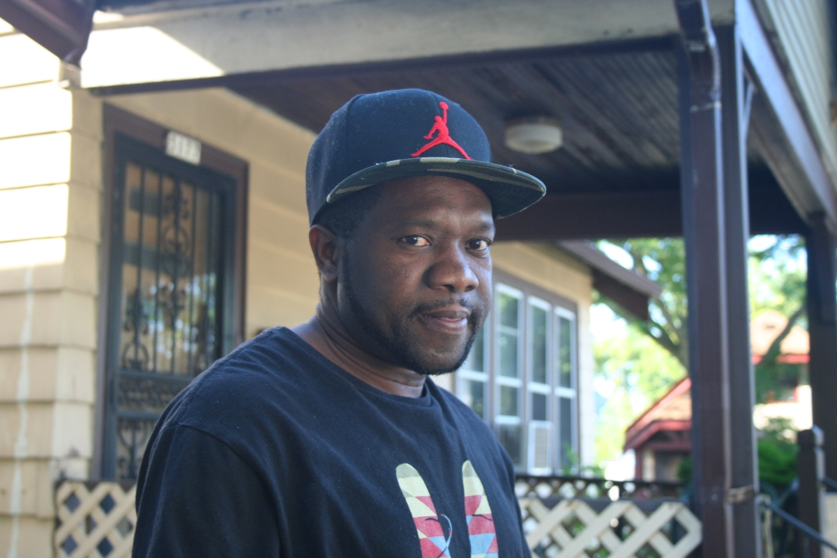 Omar Gayle, 40, stands on a porch in Sherman Park. (Photo by Jabril Faraj)