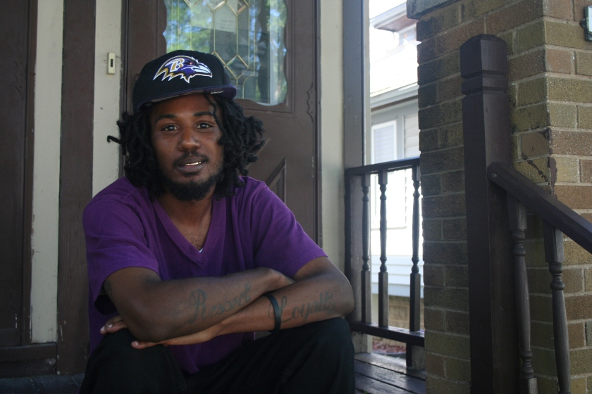Chris Sims sits on a porch in Sherman Park. (Photo by Jabril Faraj)
