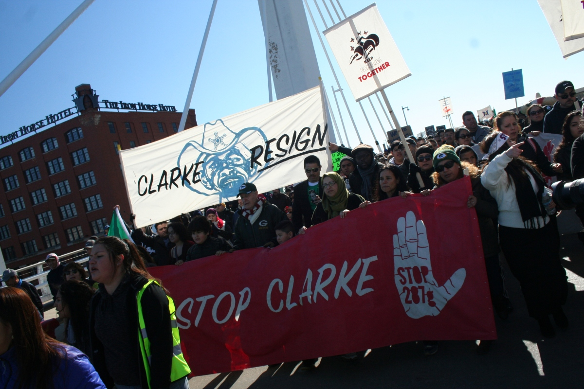 Protestors carry an anti-Clarke banner. (Photo by Jabril Faraj)
